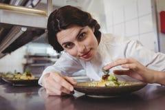 Żeński szef kuchni egzamininuje zakąska talerza przy rozkaz stacją Obraz Royalty Free
