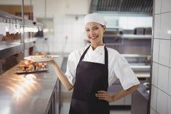 Żeński szef kuchni pokazuje karmowego naczynie kamera w handlowej kuchni Zdjęcia Stock
