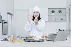 Żeński szef kuchni z babeczką pokazuje OK znaka Zdjęcie Stock
