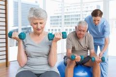 Żeński terapeuta pomaga starszej pary z dumbbells zdjęcia royalty free