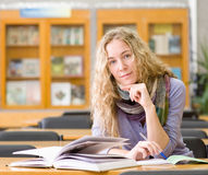 Żeński uczeń czyta książkę w bibliotece Zdjęcia Royalty Free