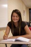 Żeński uczeń ono uśmiecha się przy jej biurkiem Zdjęcie Royalty Free