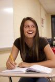 Żeński uczeń ono uśmiecha się przy jej biurkiem Zdjęcia Royalty Free