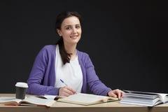 Żeński uczeń ono uśmiecha się z książką w sala lekcyjnej biurku Zdjęcie Royalty Free