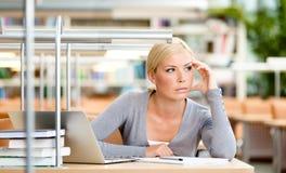 Żeński uczeń pracuje przy biurkiem fotografia stock