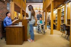 Żeński uczeń przy bibliotecznym kontuarem Obraz Royalty Free