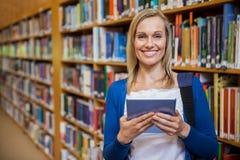Żeński uczeń używa pastylkę w bibliotece Zdjęcie Stock