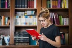 Żeński uczeń w bibliotece z książką w rękach obraz royalty free