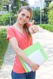 Żeński uczeń w czerwonej koszula na kampusie pokazuje kciuk obrazy stock