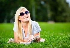 Żeński uczeń w okularach przeciwsłonecznych z książką na trawie obrazy royalty free