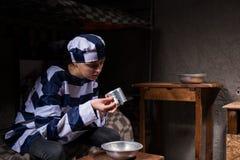 Żeński więzień jest ubranym więzienia jednolitego obsiadanie na łóżku i kantuje Obrazy Stock