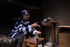 Żeński więzień jest ubranym więzienia jednolitego obsiadanie na thro i łóżku Zdjęcia Royalty Free
