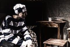 Żeński więzień jest ubranym więzienie mundur gubił w myśli podczas gdy Fotografia Stock