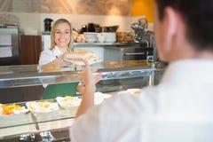 Żeński wlaściciel sklepu daje kanapce klient Fotografia Royalty Free