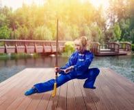 Żeński wushu wojownik z ostrzem przeciw jezioru fotografia stock