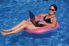 Żeński wykonawczy workaholic pracuje na laptopie w swimmi Obraz Royalty Free
