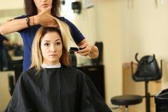 Żeńskie fryzjer ręki trzyma gręplę i włosianego kędziorek zdjęcia stock