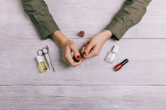 Żeńskie ręki robią manicure'u i farby gwoździom z czerwoną laką Zdjęcia Stock