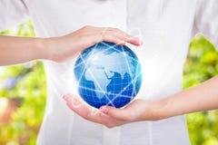 Żeńskie ręki save środowiska utrzymanie w światowej błękitnej planecie Fotografia Stock