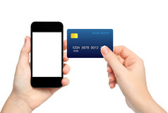Żeńskie ręki trzyma telefon i kredytową kartę na odosobnionym backgroun fotografia stock