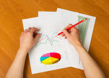 Żeńskie ręki trzymają ołówek, wykresy i prześcieradeł obliczenia na desktop, Zdjęcie Stock