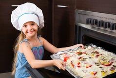 Żeńskiego dziecka wypiekowa pizza w domu Fotografia Royalty Free