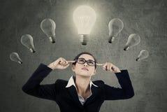 Żeńskiego kierownika myślący pomysł pod lightbulbs fotografia royalty free