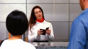 Żeńskiego lotniska pięcioliniowy sprawdzać paszportowy przy odprawy biurkiem i oddziałać wzajemnie z dojeżdżającymi zdjęcie wideo