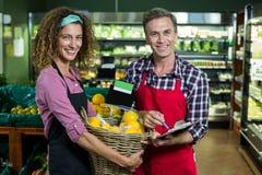 Żeńskiego personelu mienia kosz owoc i męski personel z schowkiem w supermarkecie Fotografia Stock