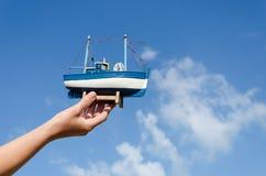 Żeńskiego ręka chwyta statku drewniana zabawka na nieba tle Zdjęcia Royalty Free