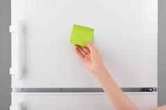 Żeńskiego ręki mienia zielonego papieru pusta notatka na białej chłodziarce Fotografia Stock
