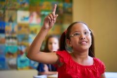Żeńskiego ucznia dźwigania ręka Podczas testa W klasie Przy szkołą zdjęcie stock