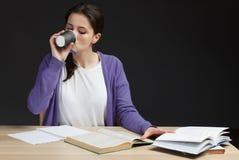 Żeńskiego ucznia drinkin kawa z książką w sala lekcyjnej biurku Zdjęcia Stock