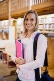 Żeńskiego ucznia mienia podręczniki w bibliotece Obrazy Stock