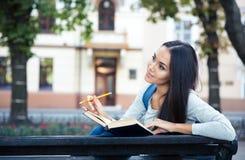 Żeńskiego ucznia obsiadanie na ławce z książką obraz stock