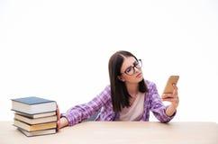 Żeńskiego ucznia pchnięcie out rezerwuje i używać smartphone Zdjęcia Royalty Free