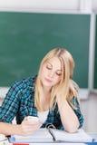 Żeńskiego ucznia wysylanie sms Na telefonie komórkowym Obrazy Stock