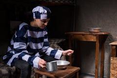 Żeńskiego więźnia łasowanie od aluminium naczyń w małym więźniarskim ce Obraz Royalty Free