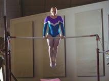 Żeńskiej gimnastyczki ćwiczy gimnastyki na horyzontalnym barze obraz stock
