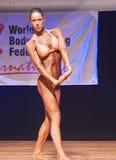 Żeńskiej postaci model napina jej mięśnie i pokazuje ona budowę ciała Fotografia Royalty Free