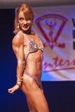 Żeńskiej postaci model napina jej mięśnie i pokazuje ona budowę ciała Zdjęcia Royalty Free