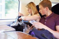 读E书的年轻夫妇在列车行程 免版税图库摄影