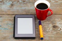 E书读者和咖啡杯在木桌上 免版税库存照片