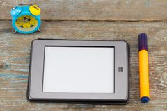 E书读者和警报在木桌上 免版税库存图片