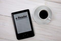 E书读者和咖啡杯在木桌上 免版税库存图片