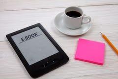 E书读者和咖啡杯在木桌上 库存图片