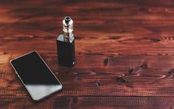 E香烟mod或电子香烟vaping的和巧妙的手机的在木 图库摄影
