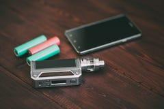 E香烟mod或电子香烟vaping的在木桌背景 免版税库存照片