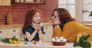 E 绘复活节彩蛋的女孩在舒适厨房里 微笑的母亲 免版税库存照片