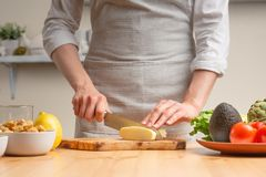 E Ένας αρχιμάγειρας κόβει το τυρί μοτσαρελών ή φέτα, ανακατώνει, κατά τη διάρκεια μιας χορτοφάγου σαλάτας στην εγχώρια κουζίνα r στοκ φωτογραφία με δικαίωμα ελεύθερης χρήσης